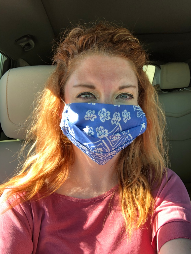 Red-haired girl in a pink shirt wearing a white a blue floral patterned face mask.