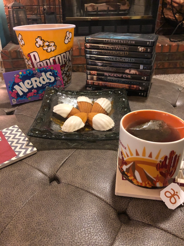 A stack of Halloween movies, with snacks including popcorn, candy, cookies, and a hot cup of tea.