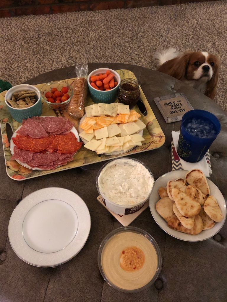 A charcuterie board including salamis, cheeses, crackers, humus, ranch dip, pita bread, carrots, and tomatoes.