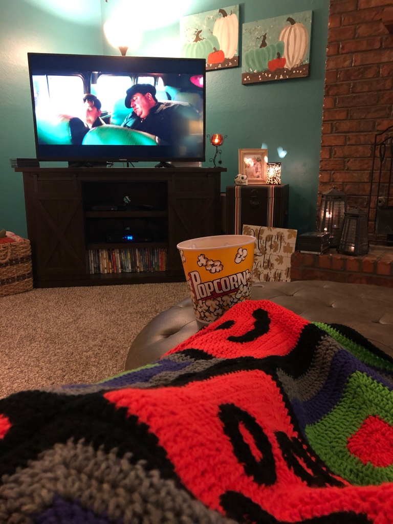 A view of the tv screen with a bucket of popcorn and a Halloween crocheted blanket in the foreground.